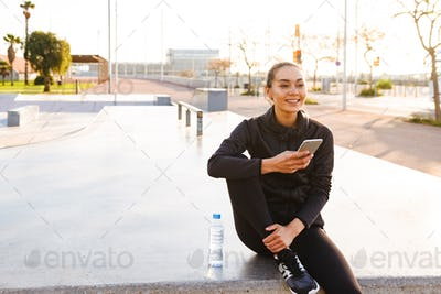 Cheerful young asian sports woman sitting outdoors