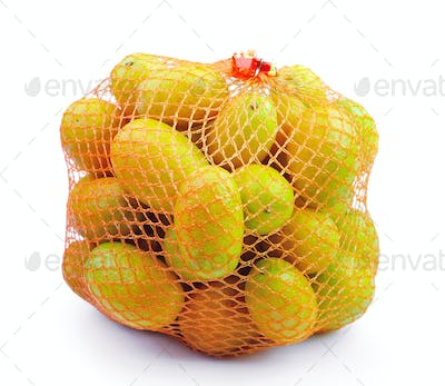 Fresh orange in plastic netting sack on white background