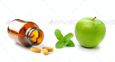 Medicine bottle of brown glass pill apple and mint  isolated on