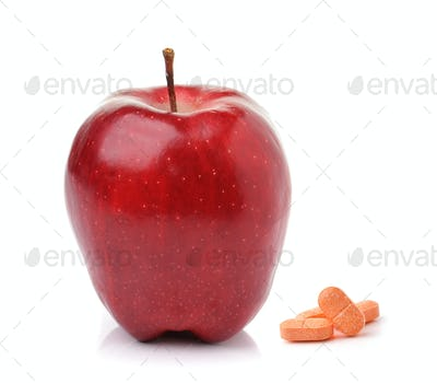 Red ripe apple  and pills capsules isolated on white background