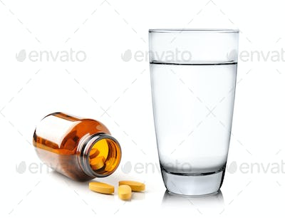 Pills from bottle and Glass of water isolated on white backgroun