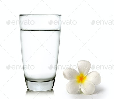 Glass of water and Tropical flowers frangipani (plumeria)
