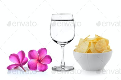 Glass of water  frangipani flower , Bowl of potato chips on whit