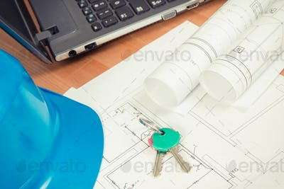 Home keys, electrical diagrams with laptop for engineer jobs and protective blue helmet