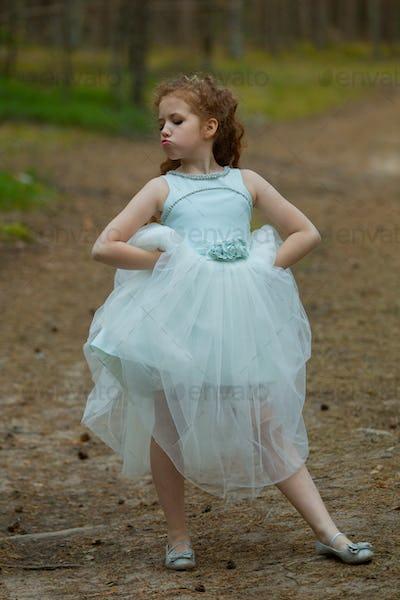 Little emotional girl walks in a summer forest in a dress