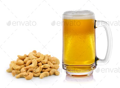 Mug fresh beer with cap of foam and cashew nuts heap on white ba