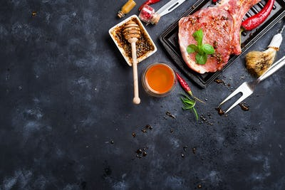 Raw steaks and frying pans with seasoning, garnishes and ingredients