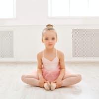 Portrait of little ballerina on floor, copy space