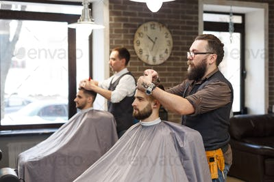 Barber make haircut with scissors to client at barbershop