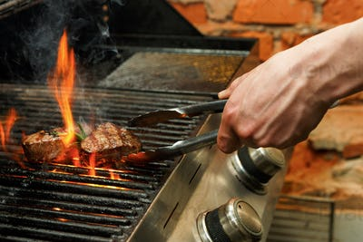 Man cooking meat steaks on professional grill outdoors