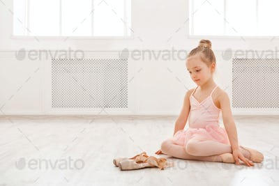 Little girl looking at pointe shoes, copy space