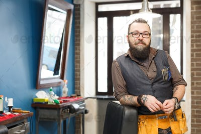 Bearded barber posing to camera at barbershop