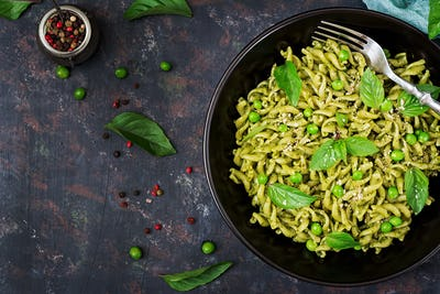 Fusilli pasta with  pesto sauce, green peas and basil. Italian food. Top view. Flat lay.