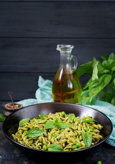 Fusilli pasta with  pesto sauce, green peas and basil. Italian food.