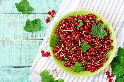 Fresh red currant in a bowl on a wooden table. Top view