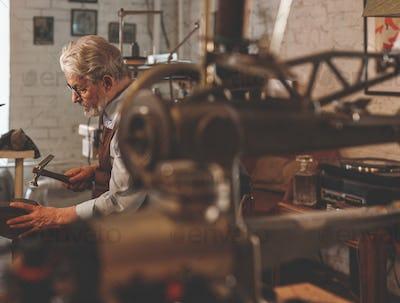 An elderly shoemaker in a workshop