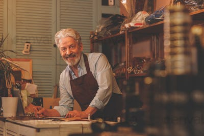 Smiling elderly shoemaker at the counter