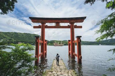 Young traveler takeing photo at red Torii gate of Hakone shrine at  lake Ashi, Japan