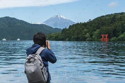 Young traveler takeing photo of  Hakone shrine with mt.Fuji at  lake Ashi, Japan