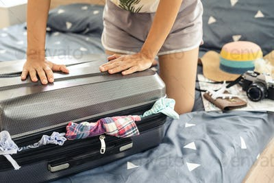 Young woman traveler packing her clothes and stuff in suitcase