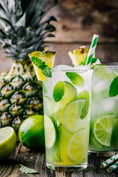 Pineapple lemonade with lime slices and mint in glass