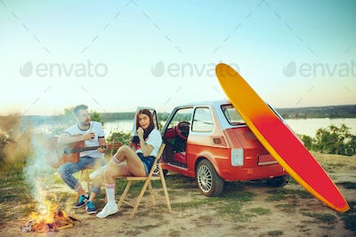 Couple sitting and resting on the beach playing guitar on a summer day near river