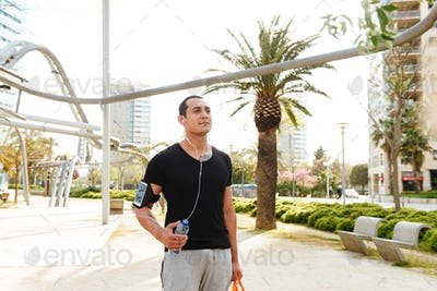 Handsome young strong sports man walking outdoors