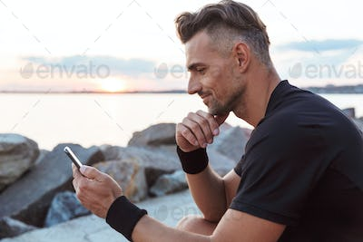 Portrait of a smiling sportsman using mobile phone