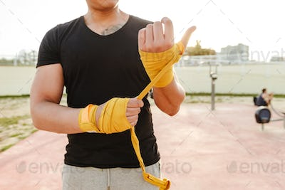 Cropped photo of young strong sports man boxer