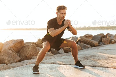Handsome sportsman make sport exercises outdoors early morning.