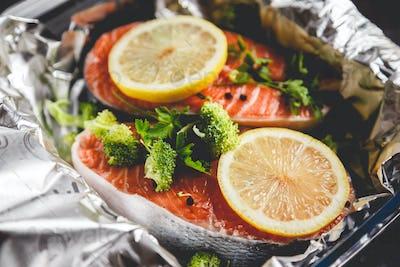 Raw sockeye salmon steaks on foil before baking in oven