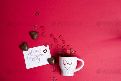 Valentine's Day with cup coffee and wooden hearts on a red background,