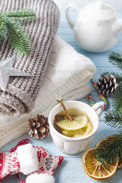 A cup of tea for the new year. A cozy plaid, a knitted scarf and hot tea on blue wooden background