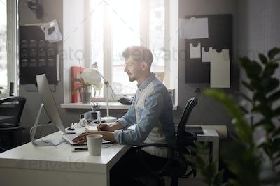 Young intelligent bearded man working at modern loft studio-offi