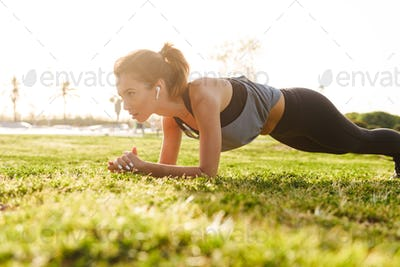 Young fitness woman make sport plank exercises