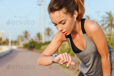 Young sports woman runner standing outdoors