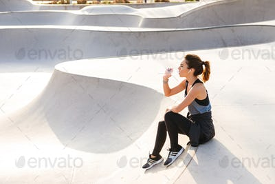Serious young sports woman sitting outdoors drinking water.