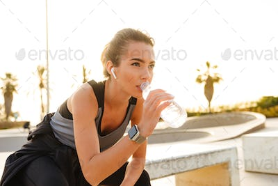 Serious young sports woman sitting outdoors