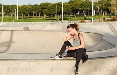 Tired sports lady sitting outdoors in park using mobile phone