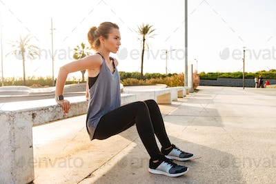 Photo of young caucasian girl in sportswear squatting and doing
