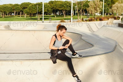 Young sports lady sitting outdoors in park