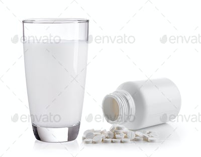milk and pills on white background