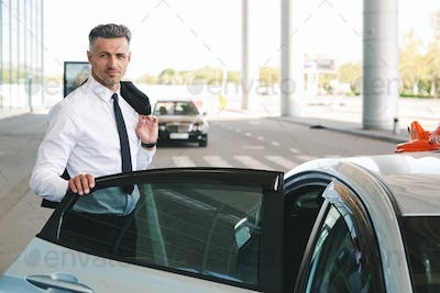 Smiling mature businessman getting in taxi outside