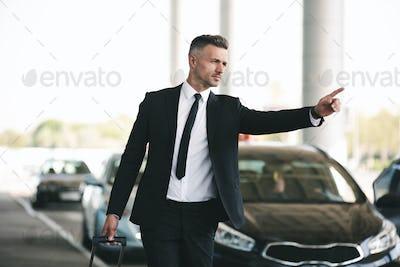 Confident mature businessman catching a taxi