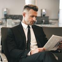 Successful businessman reading newspaper