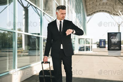 Serious businessman dressed in suit walking