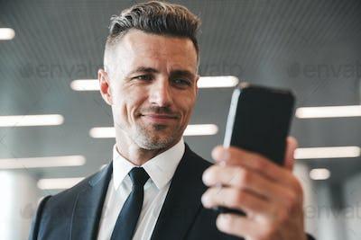 Smiling mature businessman looking at mobile phone