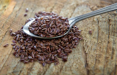 flaxseeds in spoon on wood table