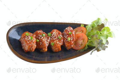 Chicken wings with sauce in ceramic plate on white background