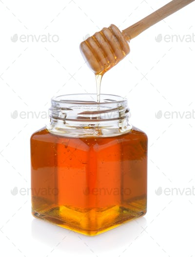 Honey with wooden honey dipper on jar